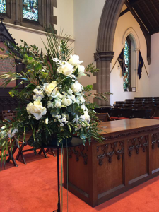 White funeral flowers on the alter at St Michael's Church