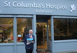Stuart Montgomery standing outside St Columba's Hospice Bookshop holding a copy of Edinburgh : The Silent City